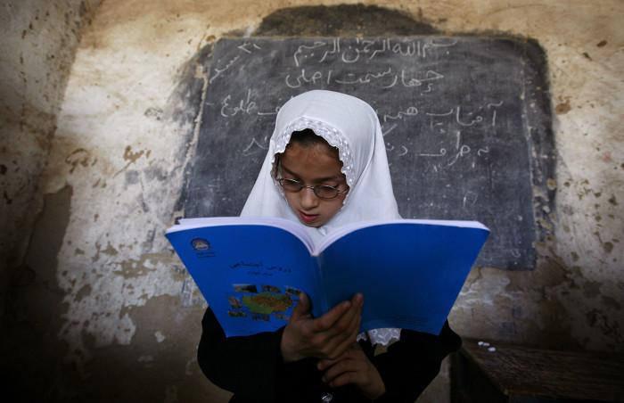 An Afghan girl reads in front her class at the girls high school Ayeshe...